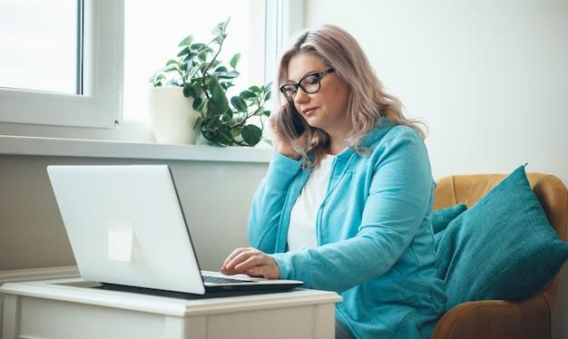 Kaukasische senior zakenvrouw met bril en blond haar is praten over de telefoon tijdens het werken op afstand met een laptop Premium Foto
