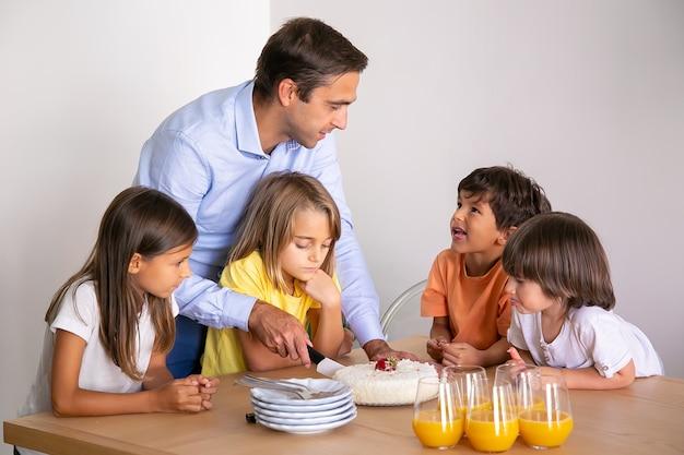 Kaukasische vader die heerlijke cake voor kinderen snijdt. schattige kleine kinderen rond tafel, samen verjaardag vieren, praten en wachten op een toetje. jeugd, feest en vakantie concept Gratis Foto