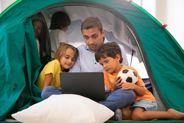 Kaukasische vader zitten met gekruiste benen met kinderen in tent thuis en kijken naar film via laptop. lieve kinderen vader knuffelen, plezier maken en spelen. jeugd, familie tijd en weekend concept Gratis Foto