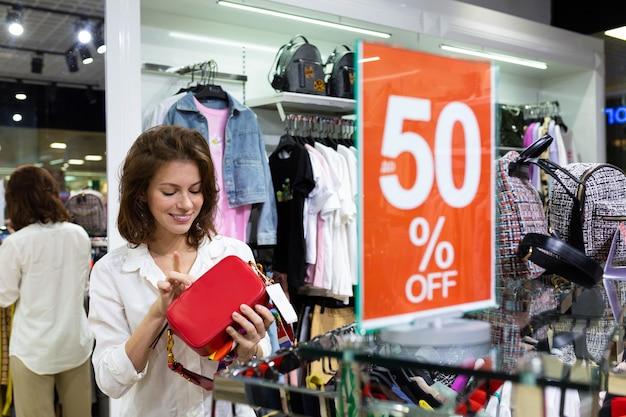 Kaukasische vrouw die heldere rode beurszak in haar hand met mooie glimlach houdt. verkoop seizoen teken. Premium Foto