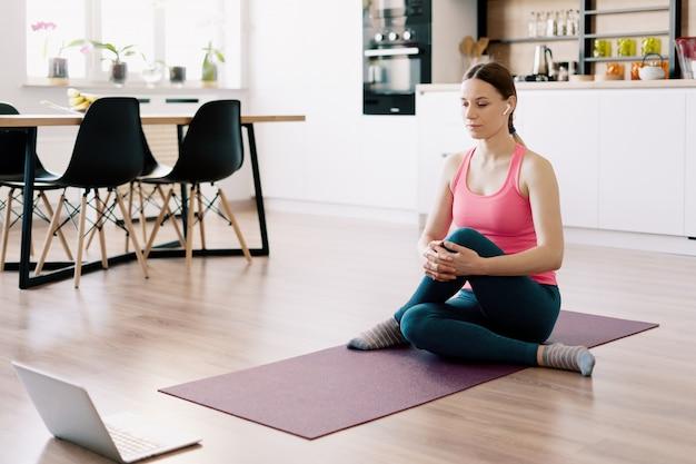 Kaukasische vrouw het beoefenen van yoga thuis Gratis Foto