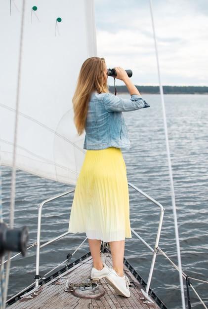 Kaukasische vrouw verrekijker kijken op de zeilboot Premium Foto