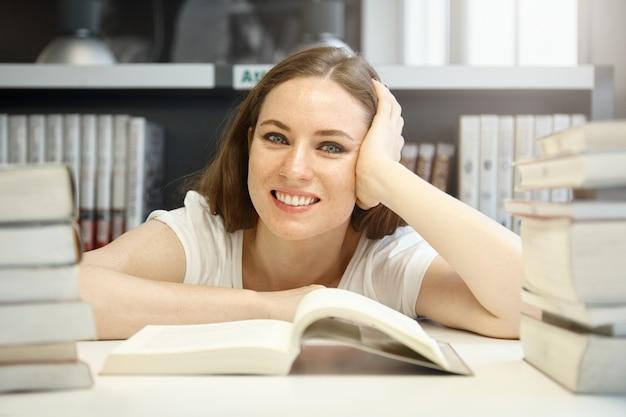 Kaukasische vrouwelijke student met een goed humeur die de vereiste informatie over geschiedenis probeert te vinden, een leerboek bestudeert, in de bibliotheek voor stapels boeken zit, lacht, er blij en tevreden uitziet Gratis Foto