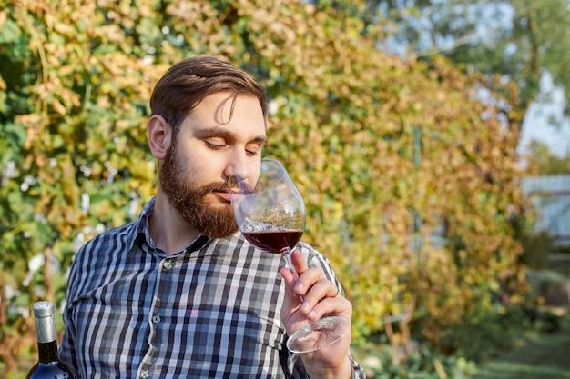 Kaukasische wijnmaker drinkglas rode wijn, proeverij het controleren van kwaliteit staande in wijngaarden Premium Foto