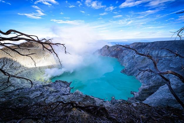Kawah ijen-vulkaan met dode bomen op blauwe hemelachtergrond in java, indonesië. Premium Foto