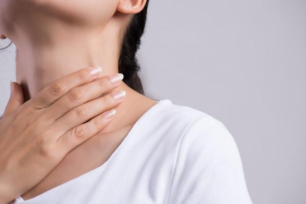 Keelpijn. close-up vrouw hand aanraken haar zieke nek Premium Foto