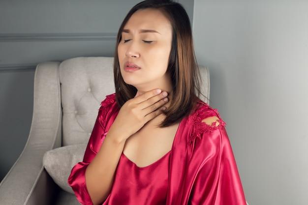 Keelpijn symptomen. keelontsteking. een vrouw die een satijnen nachthemd en een rood kleed draagt dat 's nachts in de woonkamer lijdt aan heesheid of laryngitis. Premium Foto