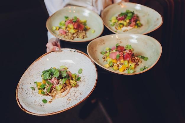 Kelner die een plaat met vis en salade op een huwelijk draagt. Premium Foto