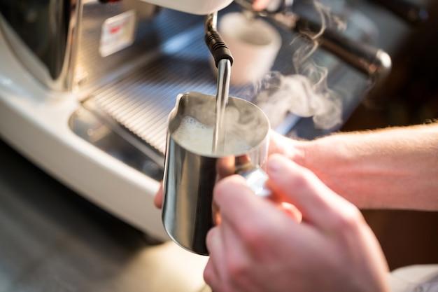 Kelner die melk stomen bij de koffiemachine Premium Foto