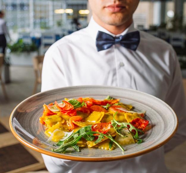 Kelnersmens die een grote plaat van ravioli met rucolabladeren houden, parmezaanse kaaskaas Gratis Foto