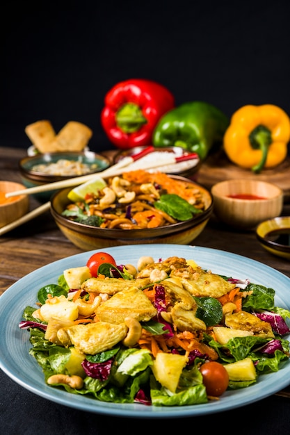 Keramiekplaat van kippensalade met noedels op bureau Gratis Foto