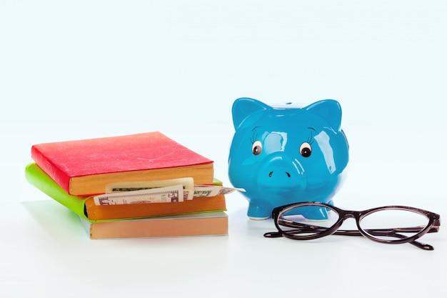 Keramisch spaarvarken met boeken en geld Premium Foto