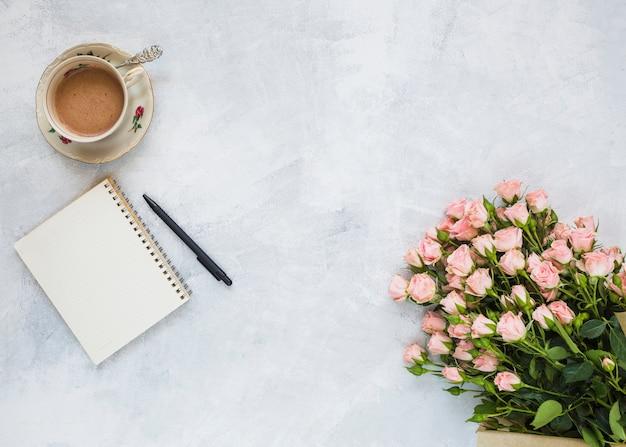 Keramische koffiekop; spiraal notitieblok; pen en bloemboeket op concrete achtergrond Gratis Foto