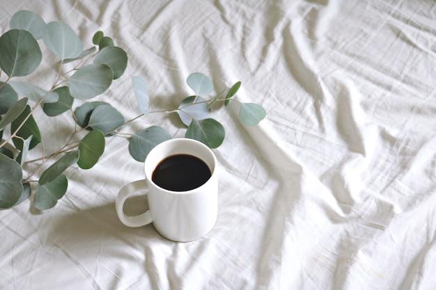Keramische mok met koffie en zilver dollar gom bladeren Gratis Foto