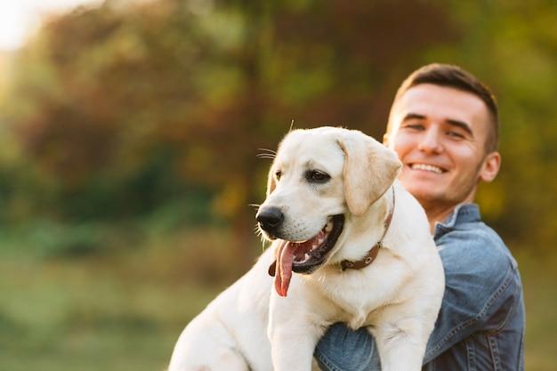 Kerel die zijn vriendhond labrador houdt en bij zonsondergang glimlacht Gratis Foto