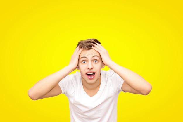 Kerel in wit in een wit t-shirt houdt zijn hoofd, geïsoleerd op een gele achtergrond Premium Foto