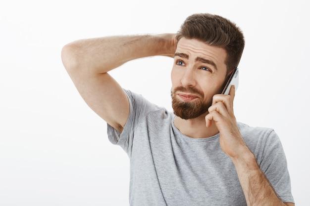 Kerel intens, onhandig probeert nee te zeggen tijdens een telefoongesprek. onzeker aarzelend knappe vriendje met baard en zieke wenkbrauwen krabben achterhoofd omhoog staren met mobieltje bij oor beslissen hoe antwoord Gratis Foto