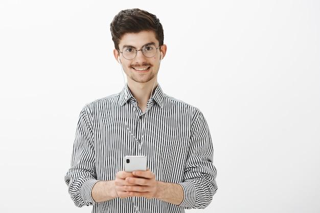 Kerel maakt aantekeningen tijdens het luisteren naar audioboek. portret van vriendelijke aantrekkelijke blanke man met snor en baard, oortelefoons dragen, genieten van het kijken naar geweldige video in smartphone, glimlachend Gratis Foto