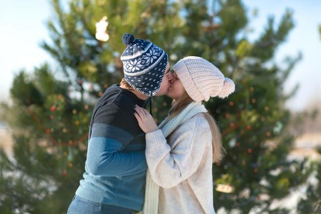 Kerel met een meisjeskus op een scène van groene die kerstboom met feestelijk speelgoed en slingers in de winter in het bos wordt verfraaid, romaanse de winter Premium Foto