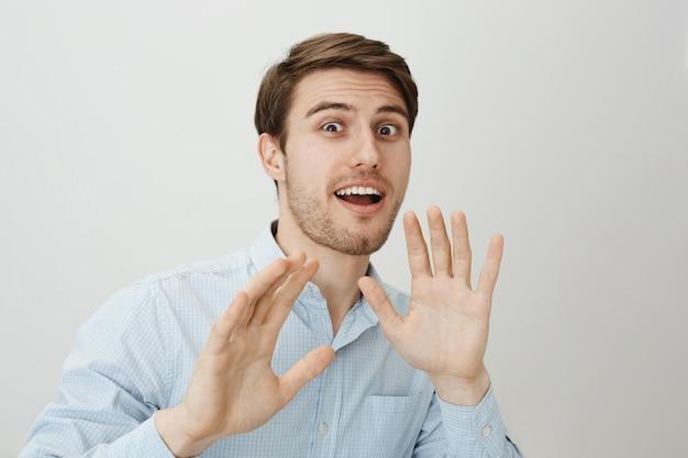 Kerel steekt zijn handen defensief op als iemand hem aanvalt Gratis Foto