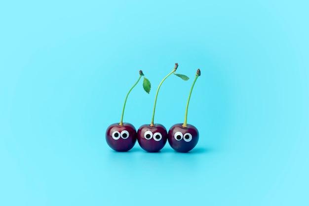 Kers met ogen op een blauwe achtergrond. grappige groenten en fruit voor kinderen. babyvoeding concept, voedsel gezicht. Premium Foto