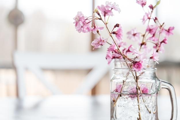 Kersenbloemen en takken in een glas water op tafel onder de lichten Gratis Foto