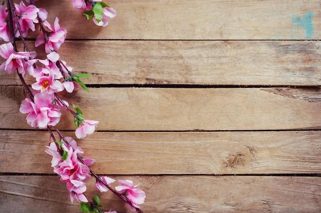 Kersenbloesem en kunstbloemen op vintage houten achtergrond met kopie ruimte. Premium Foto