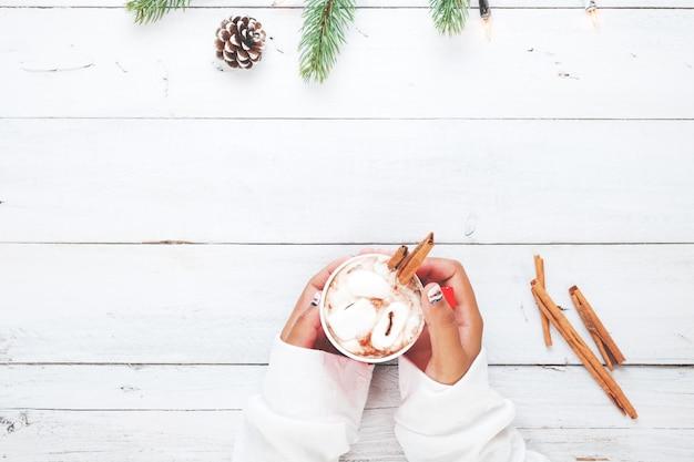 Kerst achtergrond - meisje hand houden kopje warme chocolade op witte tafel met rustieke decoratie en kopie ruimte, platte lay, bovenaanzicht. vintage kleuren toon stijl. Premium Foto