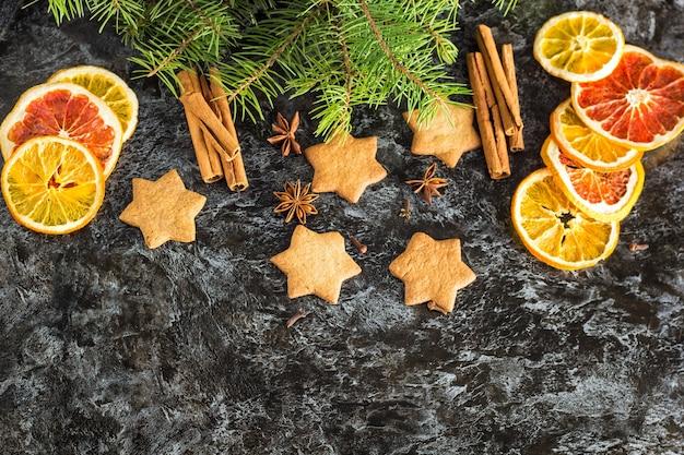 Kerst achtergrond met dennenboom droge oranje kaneel anijs en ster van peperkoek cookies op donkere achtergrond met copyspace Premium Foto