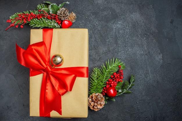 Kerst achtergrond met mooie geschenken met boogvormig lint en dennentakken decoratie accessoires aan de rechterkant op een donkere tafel Gratis Foto