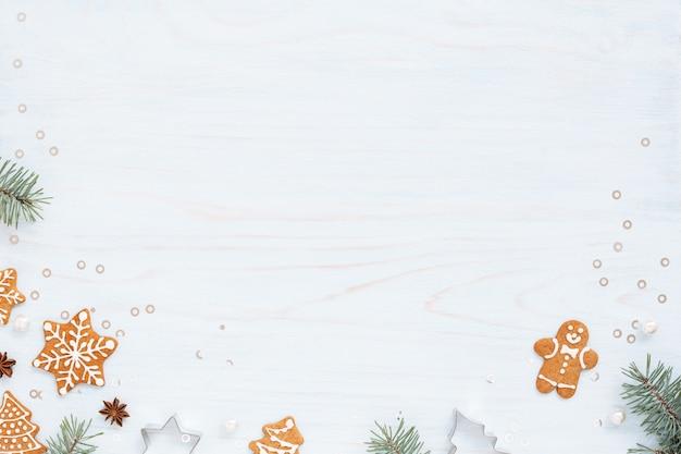Kerst achtergrond met peperkoek, sparren en decoraties op lichtblauwe tafel Premium Foto