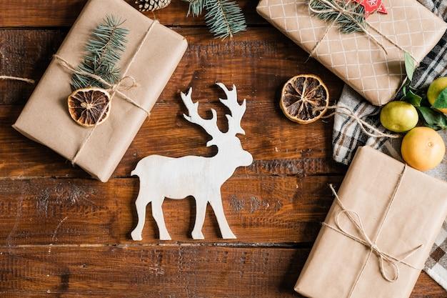 Kerst achtergrond met witte speelgoed herten, ingepakte geschenkdozen, clementines en decoraties op tafel Premium Foto