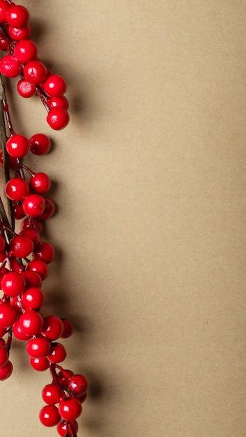 Kerst ambachtelijke bruine banner met plaats voor tekst of kopie ruimte met takken van rode bessen of viburnum aan de linkerrand. verticaal Premium Foto