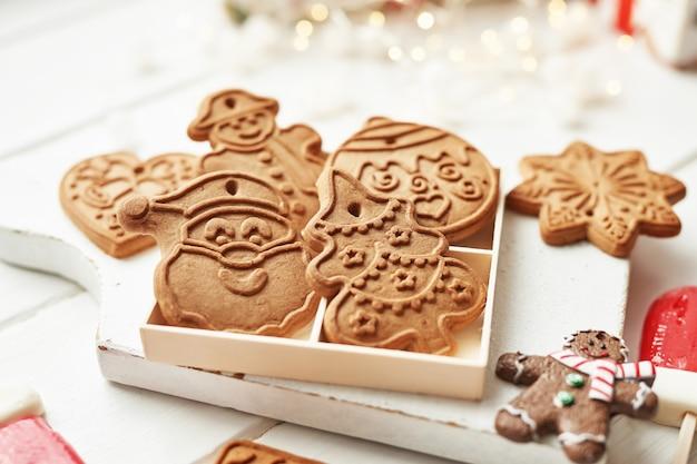 Kerst ansichtkaart template. peperkoekkoekjes op witte lijst. sneeuwvlok, santa, man, snoep vormen. kerstmiskoekjes op witte houten lijst. kerstkoekjes met feestelijke decoratie Premium Foto