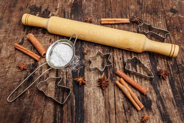 Kerst bakken, bakken, kruiden, koekjessnijders - sterren, engel en dennenboom, zeef, suikerpoeder en een deegroller. oude houten planken Premium Foto