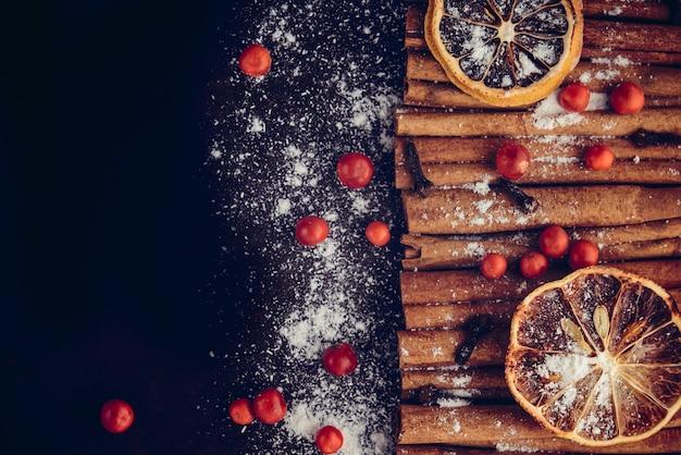 Kerst bakkerij en nieuwjaar concept. vakantie achtergrond met gedroogde citroen citrus plakjes kaneelstokjes en vanille poeder. gezellig wintervakantie bakken, glühwein frame op donkere achtergrond. Premium Foto