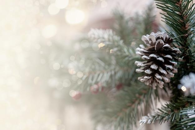 Kerst bokeh effect achtergrond met dennentakken, kegels en ruimte voor inscriptie Gratis Foto