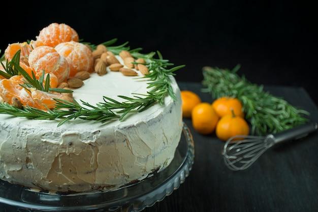 Kerst cake met mandarijnen, amandelen en rozemarijn op een stand. kerst cake met slagroom. donkere tafel. ruimte voor tekst. Premium Foto