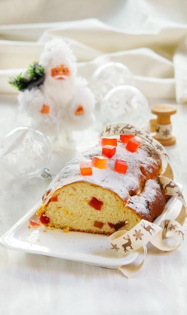 Kerst cake, versierd met suiker poeder, fruitcake op de witte stenen achtergrond Premium Foto