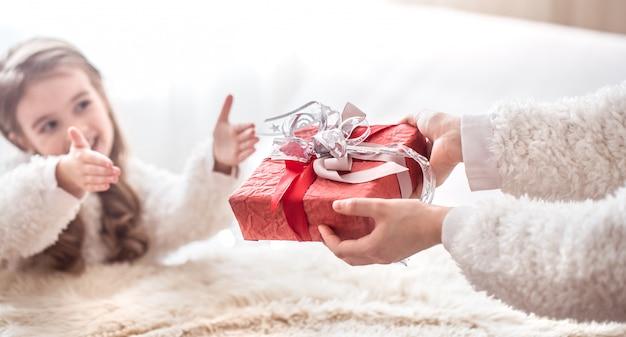 Kerst concept, moeder geeft een cadeau aan een kleine schattige dochter, een plek om te sms'en op een lichte achtergrond Gratis Foto