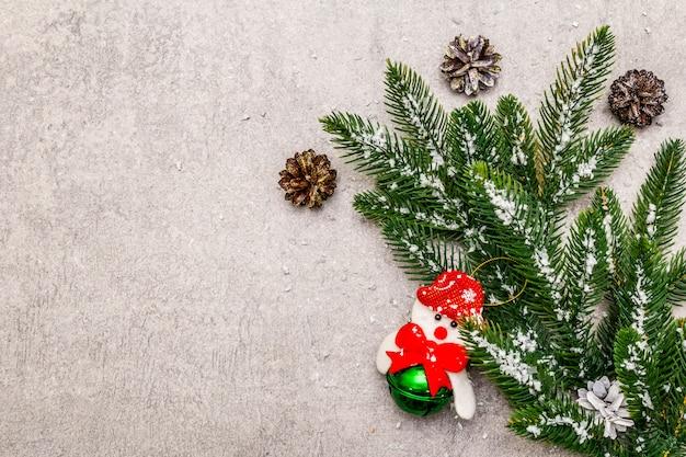 Kerst decoratie. altijdgroene sparrentak, kegels, sneeuwpop en kunstmatige sneeuw. Premium Foto