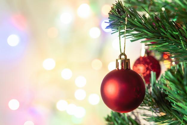 Kerst decoratie. hangende rode ballen op pijnboomtakken kerstboomslinger en ornamenten over abstracte bokehachtergrond met copyspace Premium Foto
