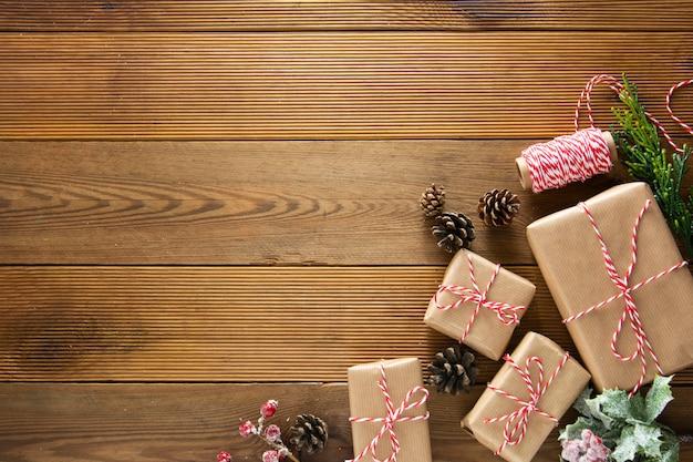 Kerst- en wintervakantie mock up. cchristmas geschenkdoos met dennenappels, fir brances, op bruin houten tafel met kopie ruimte. kerst plat lag, kopie ruimte. Premium Foto