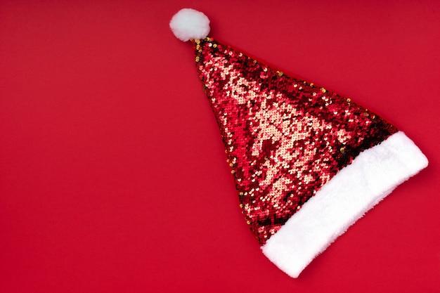 Kerst fonkelende kerstman hoed op rode achtergrond. kerstmisachtergrond van de kerstmis nieuwe jaarvakantie. nieuw jaar accessoire. merry christmas wenskaart. bovenaanzicht, plat lag, kopie ruimte Premium Foto