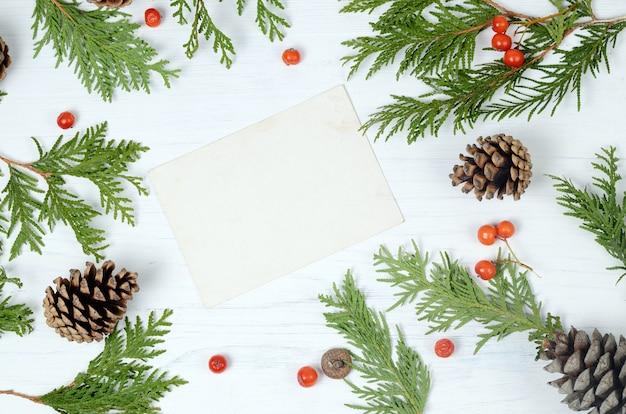Kerst frame. fir tree takken en rowan bessen op een witte achtergrond. bovenaanzicht compositie Premium Foto