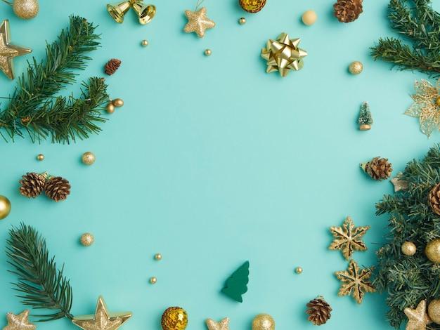 Kerst frame met gouden decoratie op lichtblauwe achtergrond, bovenaanzicht Premium Foto