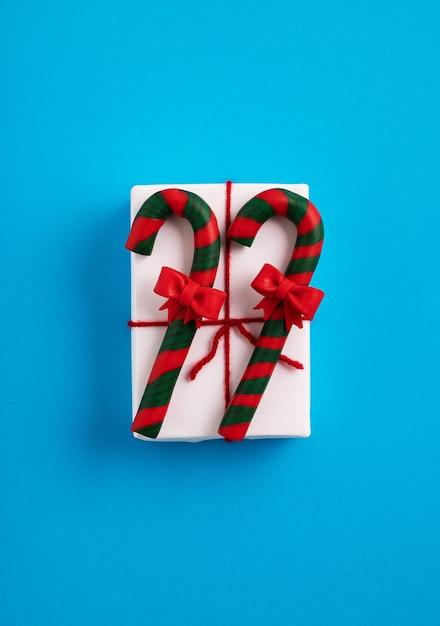 Kerst geschenkdoos met een rood lint versierd met zuurstokken Gratis Foto