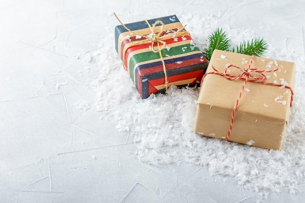Kerst geschenkdozen in kraftpapier en vuren takken op sneeuw Premium Foto