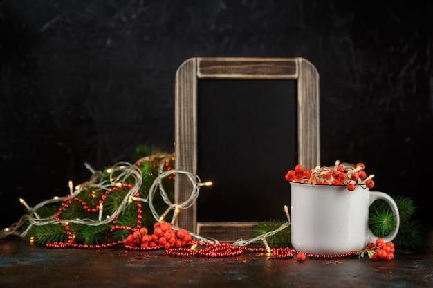 Kerst gloeiende slinger in beker, krijtbord, dennentakken en lijsterbessen op donker Premium Foto
