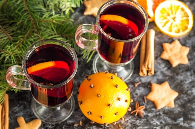 Kerst glühwein met gemberkoekjes oranje kaneel kruidnagel anijs en fir tree op de donkere tafel Premium Foto
